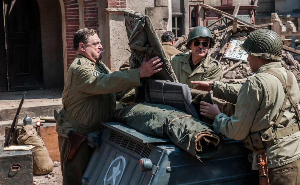 Burnt church at St Lo, Normandy - Walter Garfield (JOHN GOODMAN, left), Frank Stokes (GEORGE CLOONEY, center) and Sam Epstein (DIMITRI LEONIDAS) unload art from a kübelwagen in Columbia Pictures' THE MONUMENTS MEN. PHOTO BY:Claudette Barius COPYRIGHT:© 2013 Columbia Pictures Industries, Inc. and Twentieth Century Fox Film Corporation. All Rights Reserved.