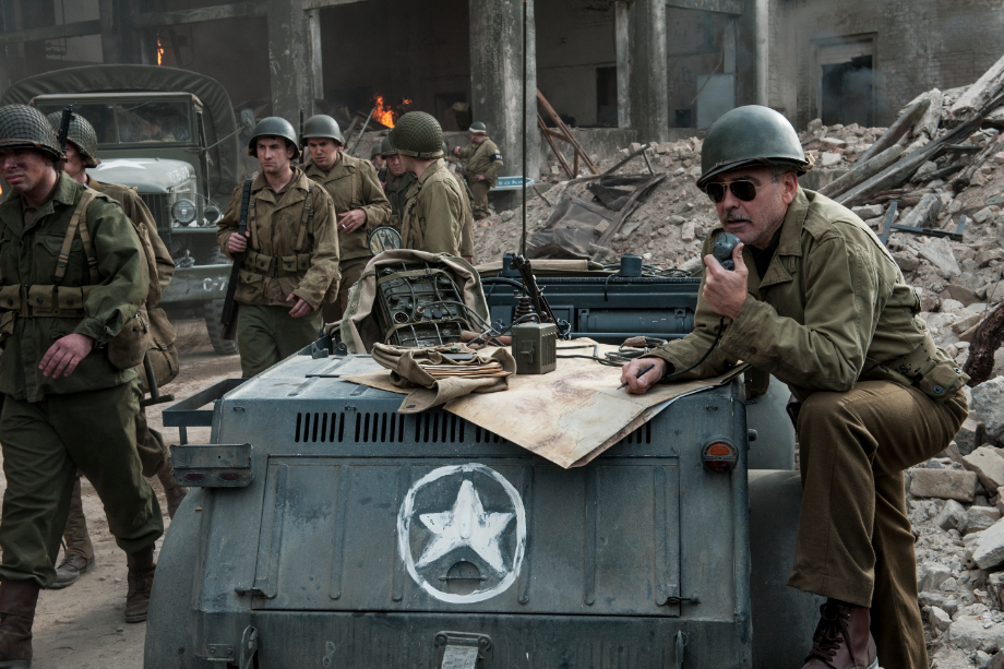 Road to St. Vith - Stokes (GEORGE CLOONEY, right) on radio as convoy of troops walks through burnded out building in Columbia Pictures' THE MONUMENTS MEN. PHOTO BY: Claudette Barius COPYRIGHT:© 2013 Columbia Pictures Industries, Inc. and Twentieth Century Fox Film Corporation. All Rights Reserved.
